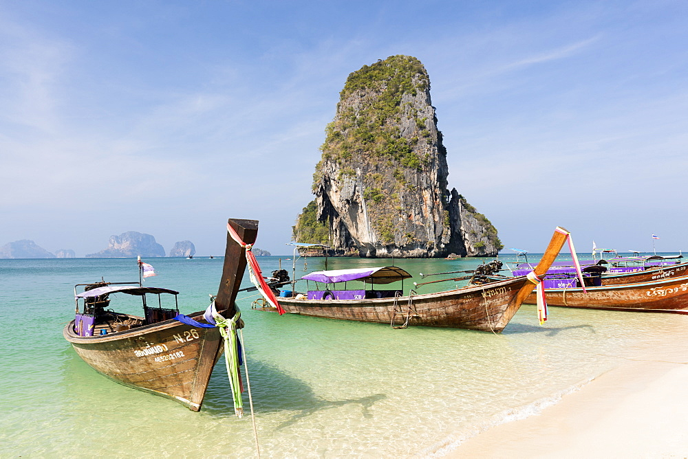 Traditional Longtail boats moored by Phra Nanag Beach with limestone islands in the background, Krabi, Thailand
