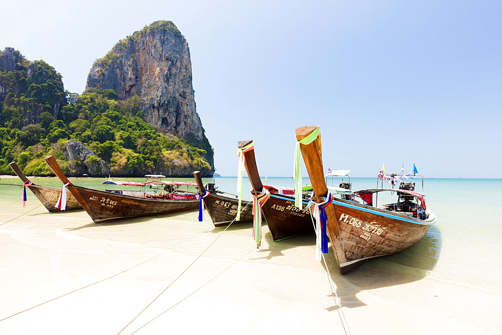 Traditional Longtail boats moored by Railay Beach with limestone cliffs in the background, Ao Nang, Krabi, Thailand