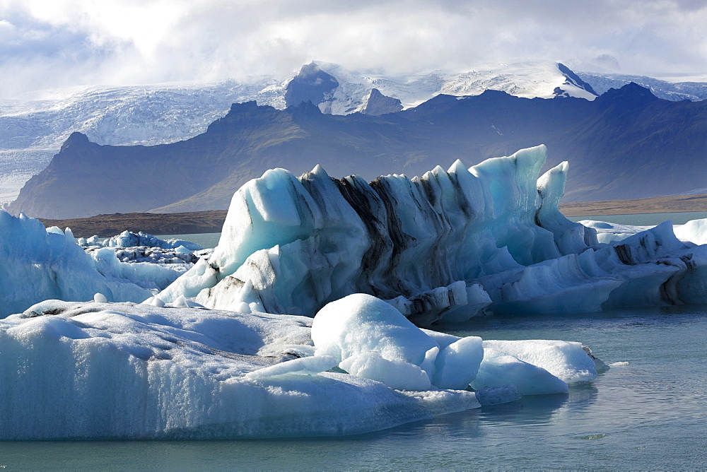 Icebergs on Jokulsarlon Glacial Lagoon, with mountains and glacier behind, South Iceland, Polar Regions