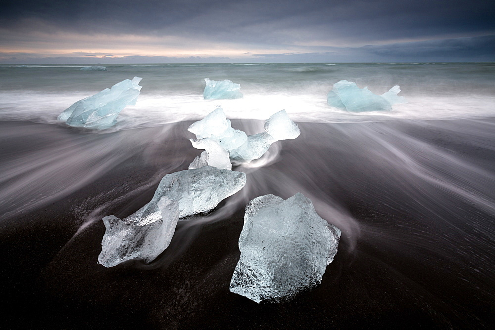 Glassy pieces of ice on volcanic black sand beach with blurred waves, near Jokulsarlon Lagoon, South Iceland