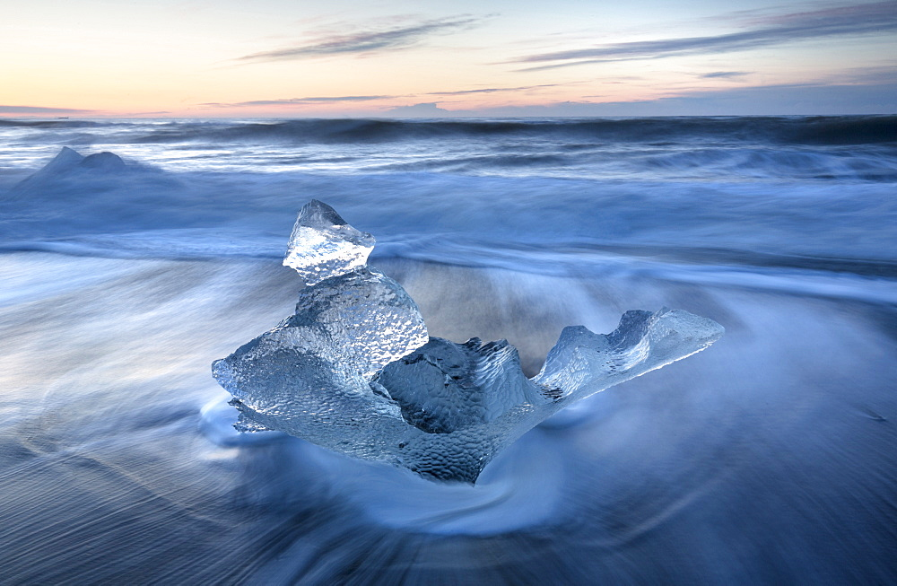 Glassy pieces of ice on volcanic black sand beach at sunrise, near Jokulsarlon Lagoon, South Iceland, Polar Regions