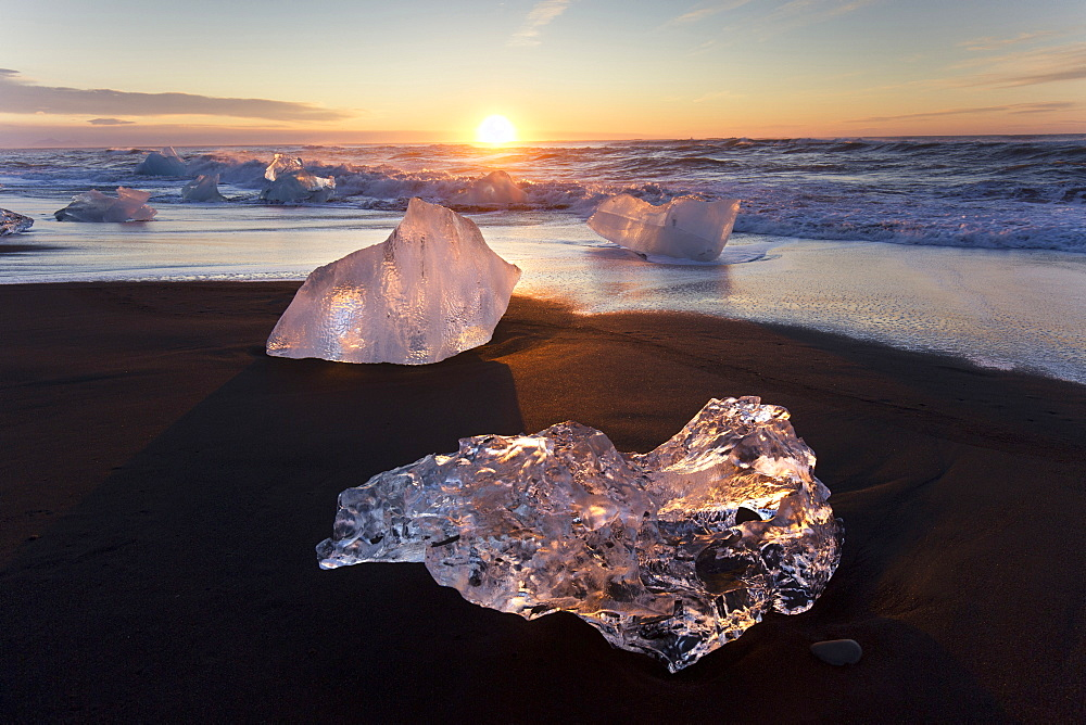 Glassy pieces of ice on volcanic black sand beach at sunrise, near Jokulsarlon Lagoon, South Iceland