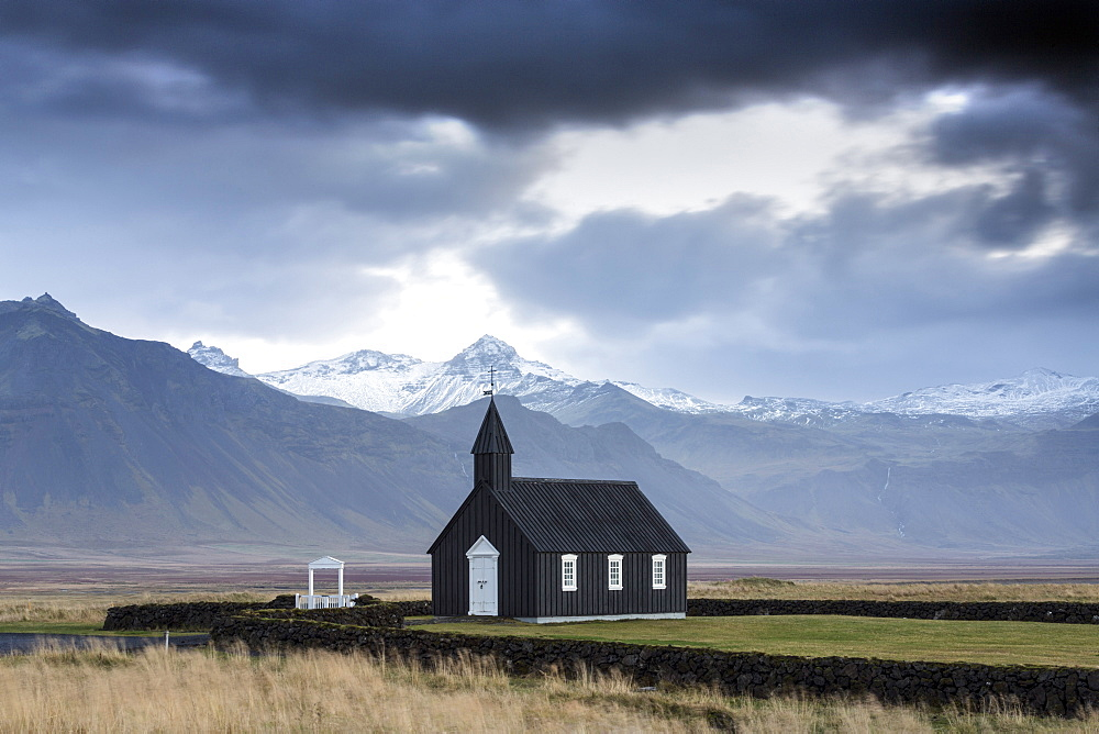Black wooden church against mountains, Budir, Snaefellsnes Peninsula, Iceland, Polar Regions