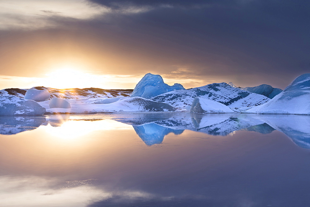 Icebergs covered in dusting of snow in winter at sunset, Jokulsarlon Glacial Lagoon, South Iceland, Polar Regions