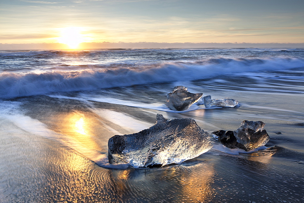 Pieces of glacier ice washed up on black volcanic sand beach at sunrise, near Jokulsarlon Glacial Lagoon, South Iceland