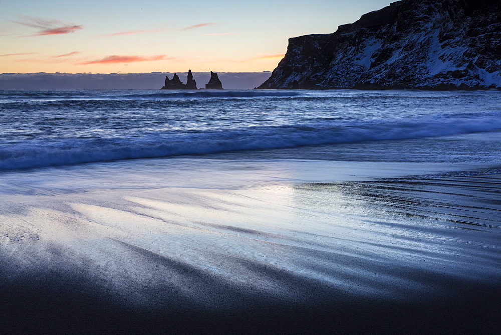 Winter sunset on black volcanic sand beach looking towards rock stacks of Reynisdrangar, Vik, South Iceland, Polar Regions