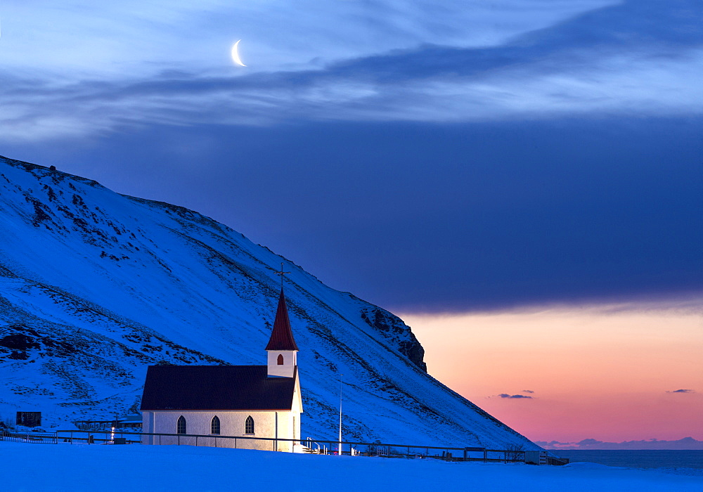 Floodlit church at dawn against snow covered mountains, winter, near Vik, South Iceland, Polar Regions