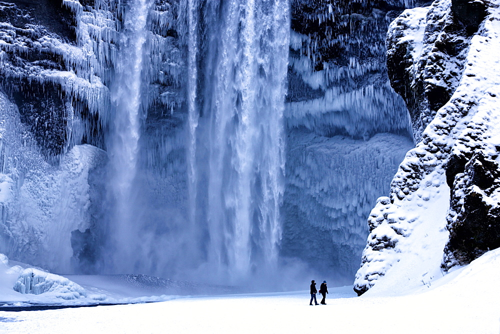 Winter view of Skogafoss waterfall, with cliffs covered in Icicles and foregreound covered in snow, Skogar, South Iceland