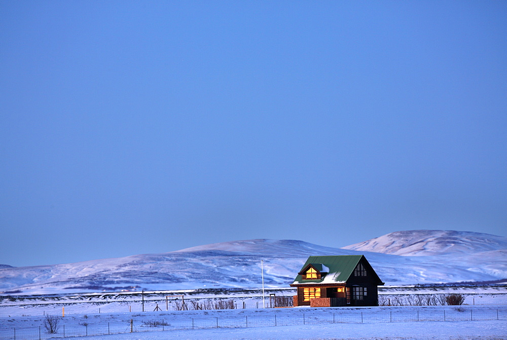 Winter landscape at dusk showing lone cabin bathed in evening sunlight, near Seljalandsfoss, South Iceland, Polar Regions