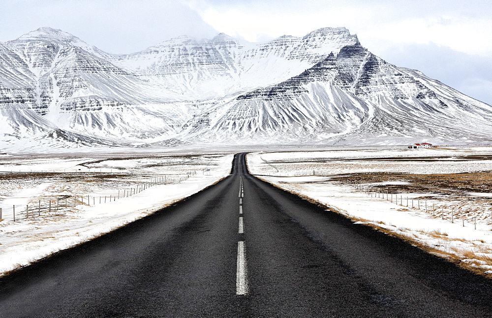 Black tarmac road leading towards snow covered mountains in winter, South Iceland, Polar Regions