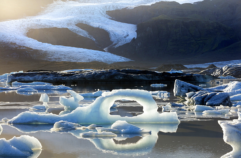 Ice arch among icebergs floating on Fjallsarlon lagoon, near Jokulsarlon, South Iceland, Polar Regions
