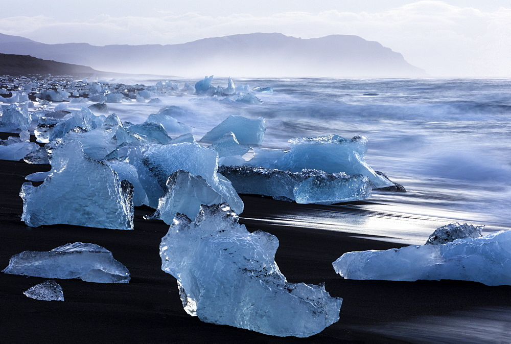 Glacial icebergs washed up from North Atlantic Ocean onto volcanic sand beach near Jokulsarlon, South Iceland, Polar Regions