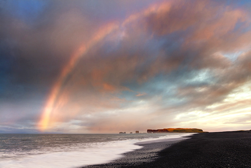 Distant view of Dyrholaey at sunrise with rainbow, from Halsanefs Hellir Beach near Vik, South Iceland, Polar Regions
