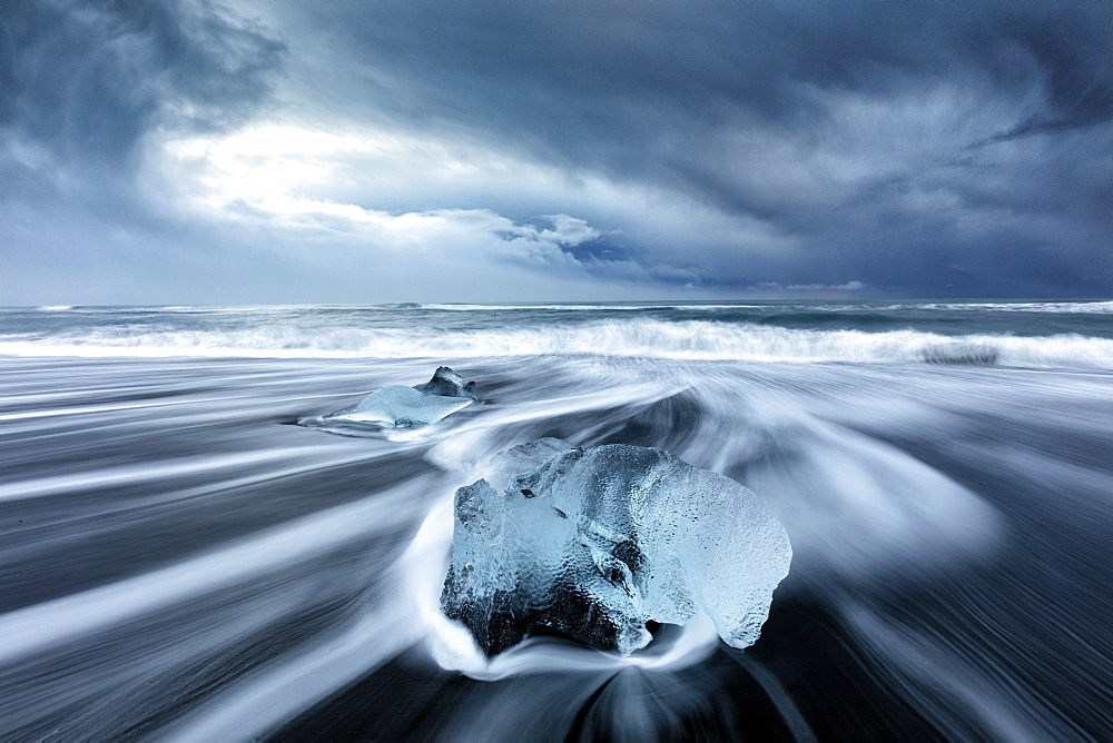 Glacier ice on black sand beach with waves washing up the beach on a stormy winter day, near Jokulsarlon, South Iceland, Polar Regions - 321-5816