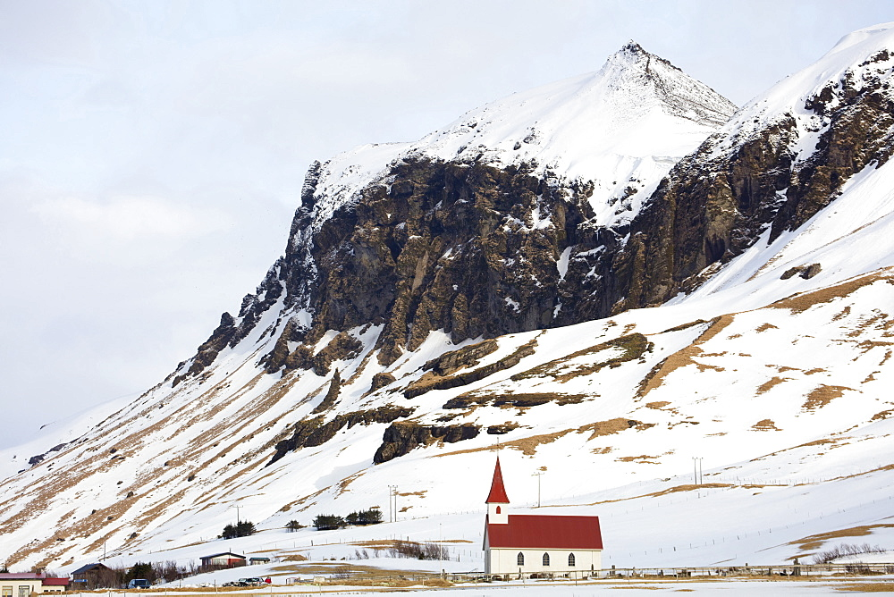 Red and white church against snow covered mountains, Vik, South Iceland