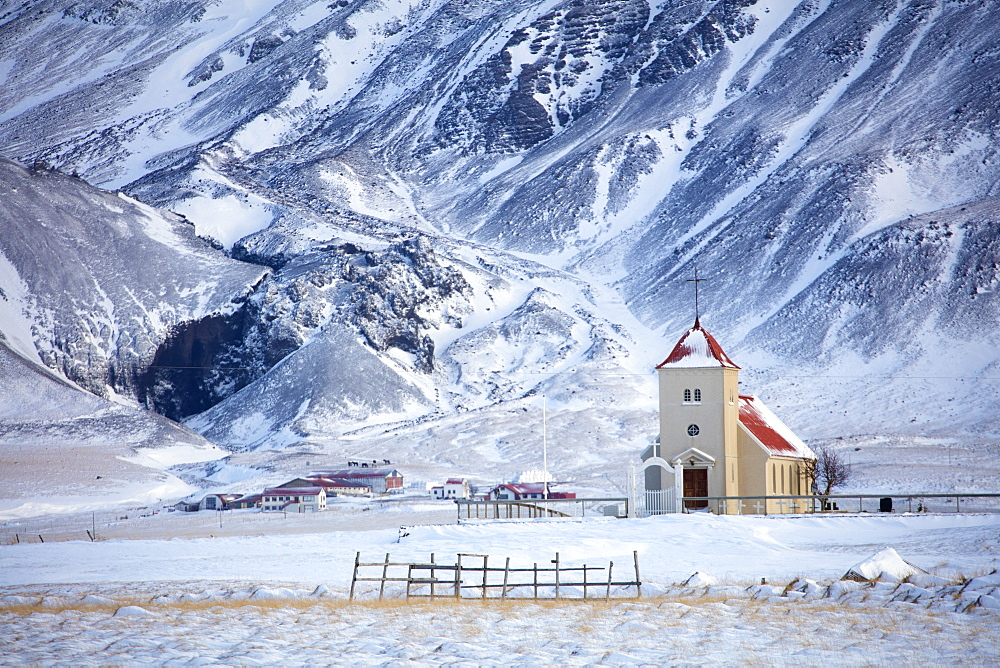 Church and isolated farm against snow covered mountains, winter's afternoon on the road to the Snaefellsnes Peninsula, Iceland