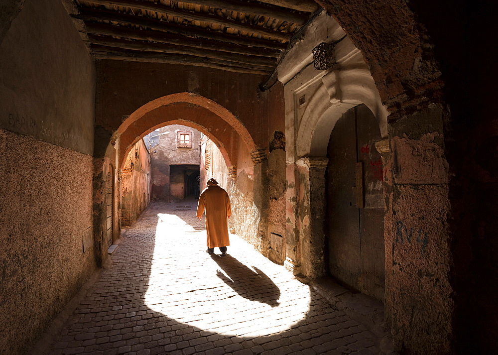 Local man dressed in traditional djellaba walking through archway in a street in the Kasbah, Marrakech, Morocco, North Africa, Africa - 321-5858