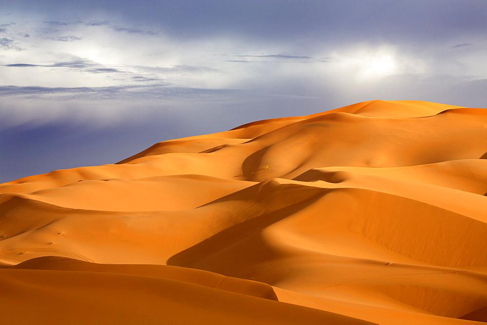 Orange sand dunes against stormy sky, Erg Chebbi sand sea, part of the Sahara Desert near Merzouga, Morocco