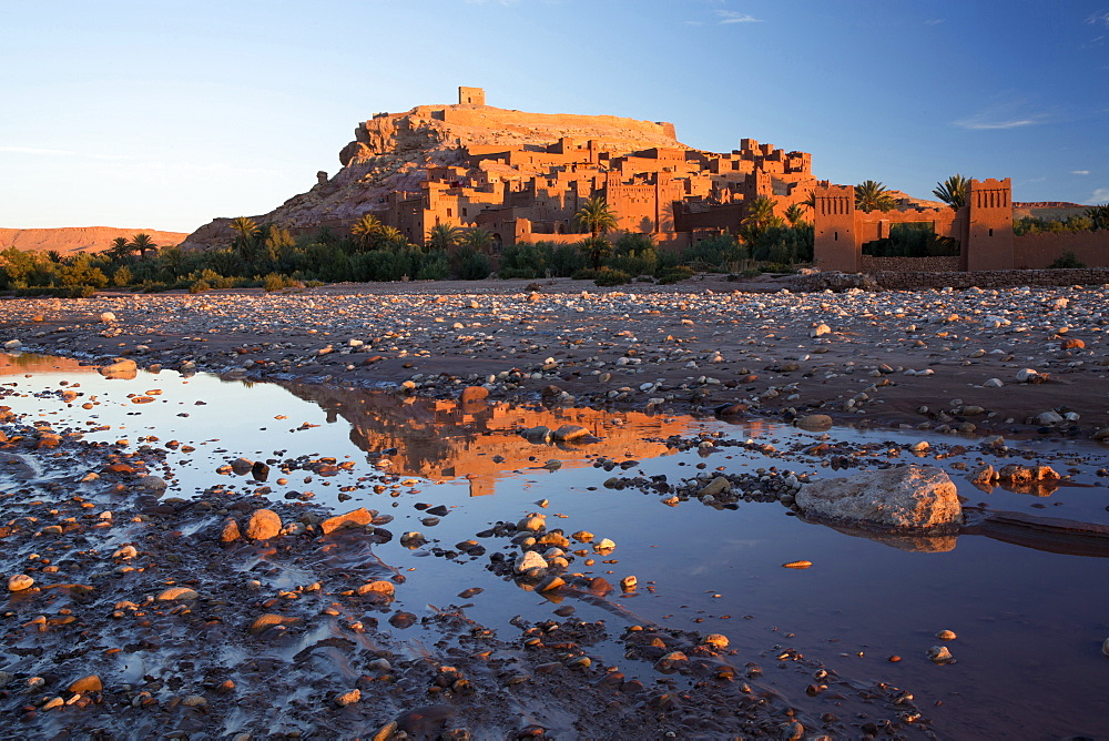 The ancient Kasbah Ait Benhaddou bathed in morning light and reflecting in river, UNESCO World Heritage Site, near Ouarzazate, Morocco, North Africa, Africa