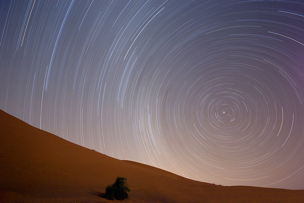 Star trails in night sky around Polaris (the pole star) over dunes of the Erg Chebbi sand sea near Merzouga, Morocco, North Africa, Africa