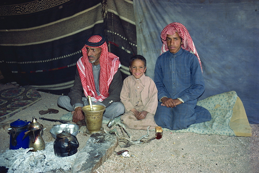 Portrait of three Bedouin sitting inside tent with tea or coffee pots and glasses in Wadi Rum, Jordan, Middle East