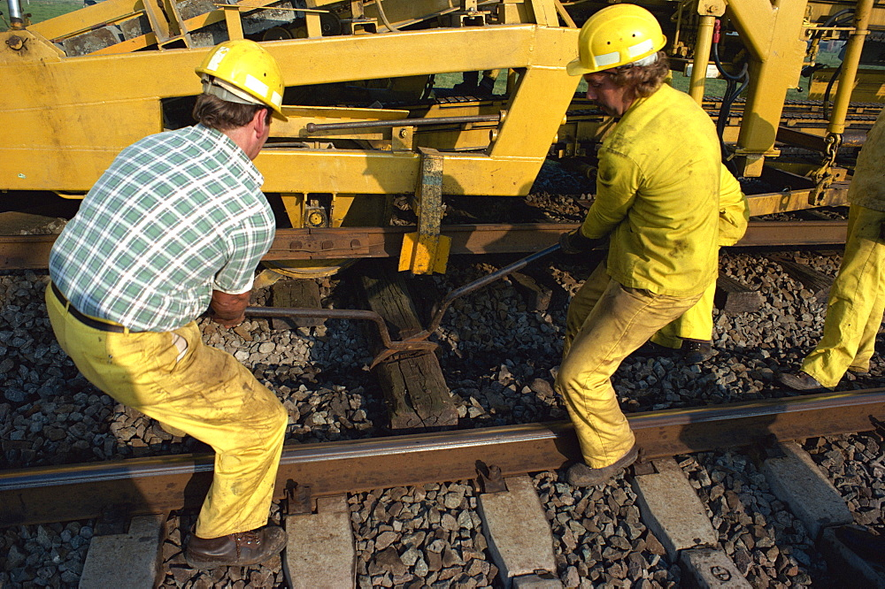 Manually removing jammed wooden sleeper from automatic pick-up mechanism during track installation, Belgian Railways, Belgium, Europe