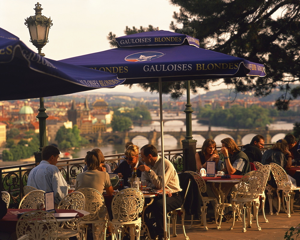 People at cafe tables in the open air at the Hanavsky Pavilion, with the river and the city of Prague behind, in The Czech Republic, Europe