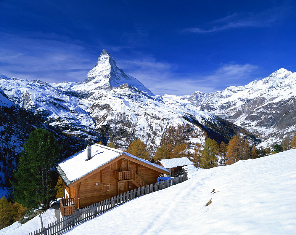 Chalets in a snowy landscape with the Matterhorn peak, near Zermatt, Swiss Alps, Switzerland, Europe