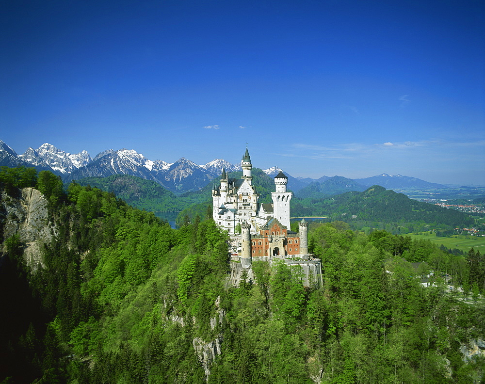 The Neuschwanstein Castle on a wooded hill with mountains in the background, in Bavaria, Germany, Europe