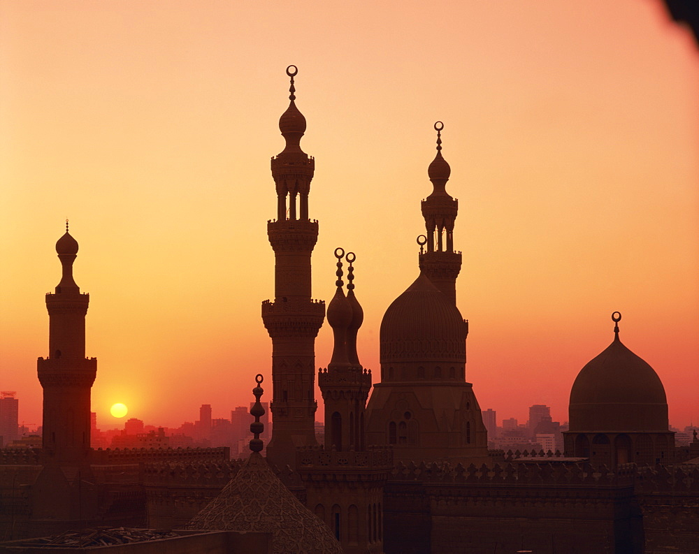 Domes and minarets silhouetted at sunset, Cairo, Egypt, North Africa, Africa
