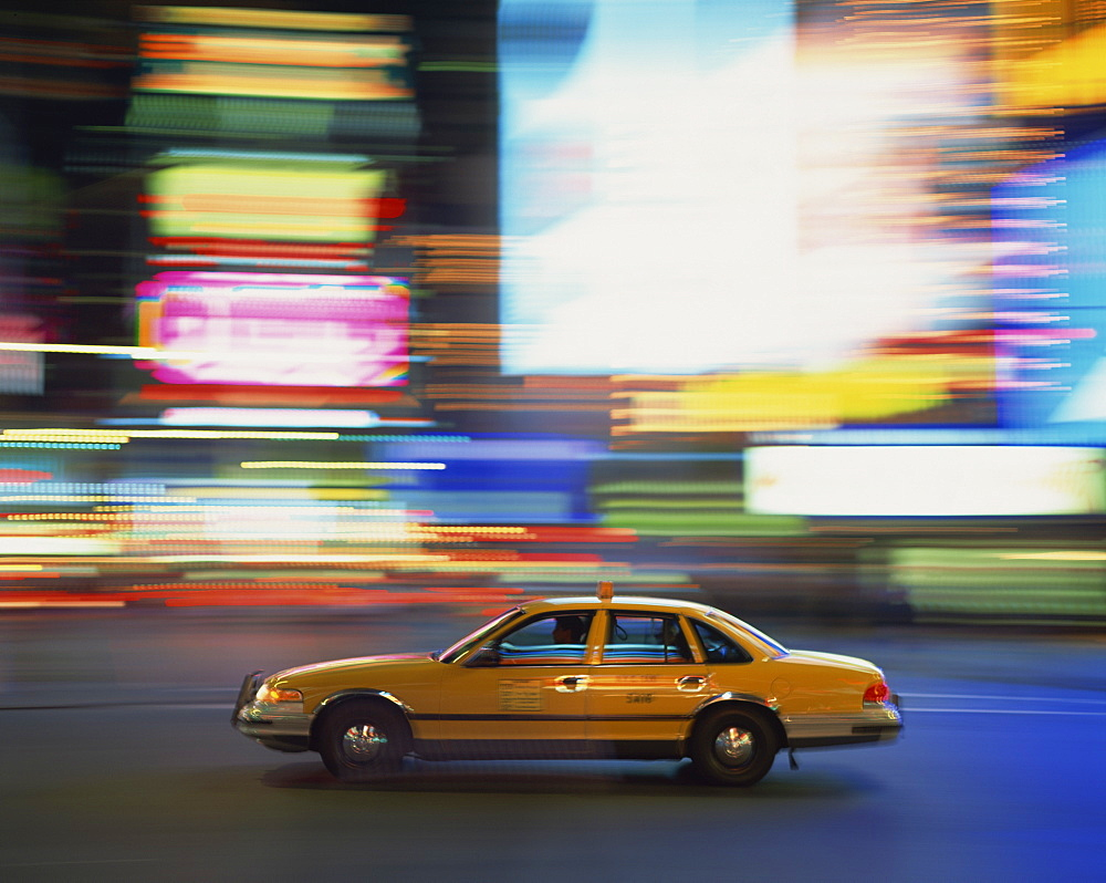 Yellow cab driving past blurred neon lights at night in Times Square in New York, United States of America, North America