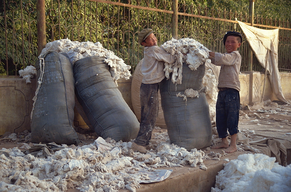 Kids packing wool at end of the day, Sunday Market, Kashgar, China, Asia
