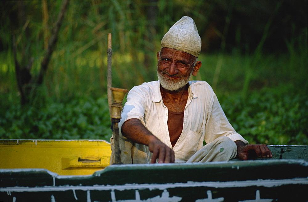 Man sitting in shikara, Dal Lake, Kashmir, India, Asia - 357-58