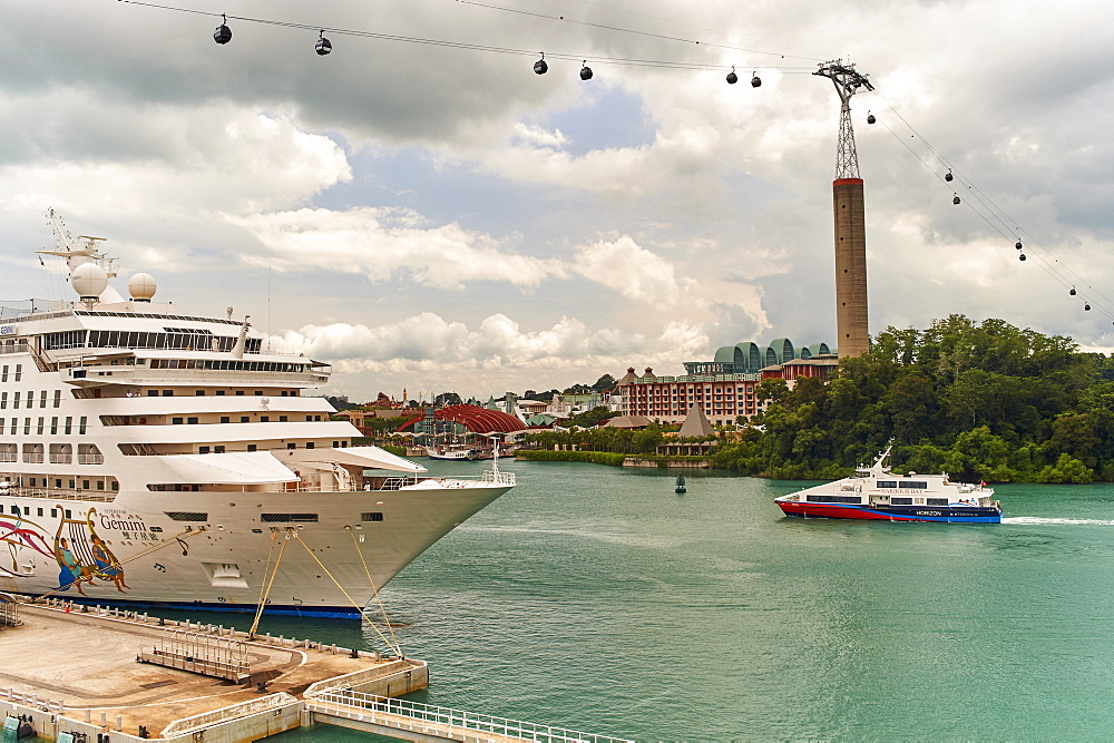 Cruise ship moored at Harbourfront Centre, Singapore, with Sentosa Island resort behind and Sky Network cable car overhead. - 358-598