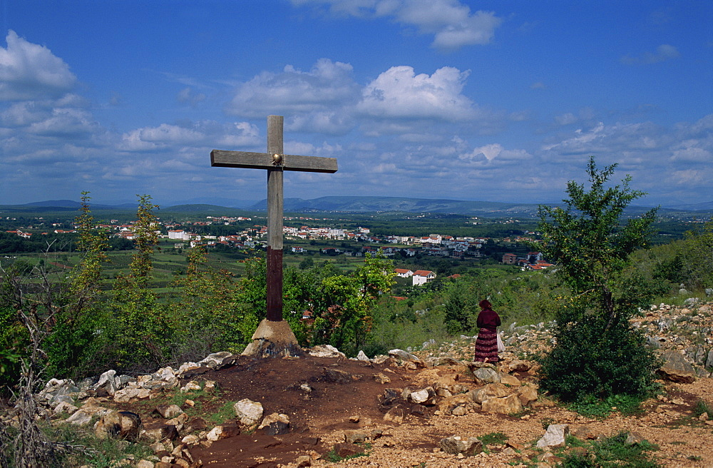Cross and pilgrim on Apparition Hill, with town beyond, Medjugorje, Bosnia Herzegovina, Europe - 365-3019