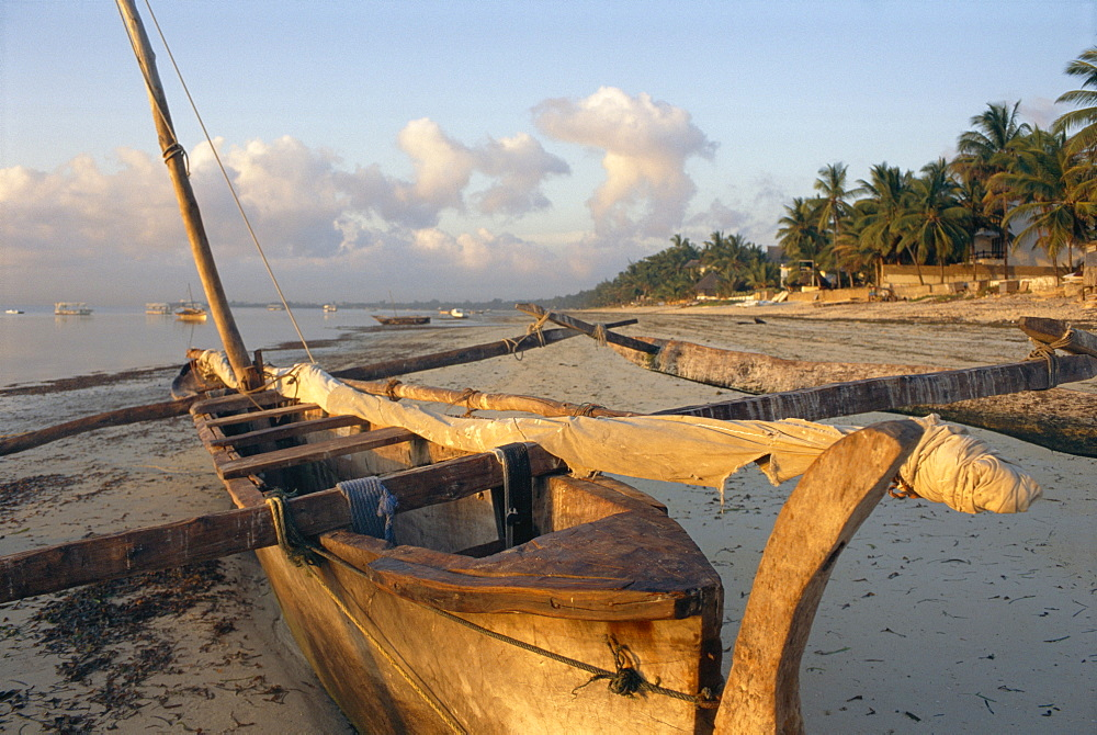 Canoe pulled up onto beach at dusk, Bamburi Beach, near Mombasa, Kenya, Africa