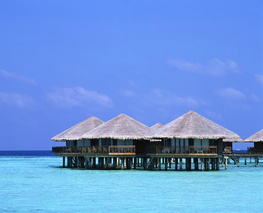 Thatched bungalows over the water in the Maldive Islands, Indian Ocean, Asia