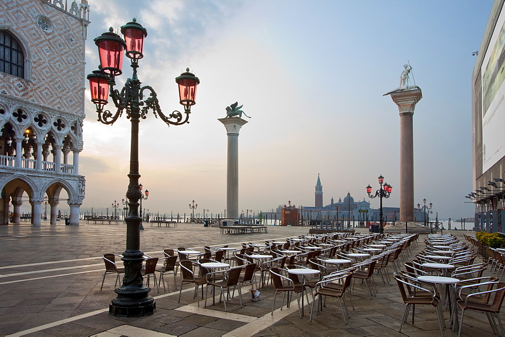Cafe tables and chairs in the early morning in St. Marks Square, with Isola di San Giorgio Maggiore in distance, Venice, UNESCO World Heritage Site, Veneto, Italy, Europe - 385-1667