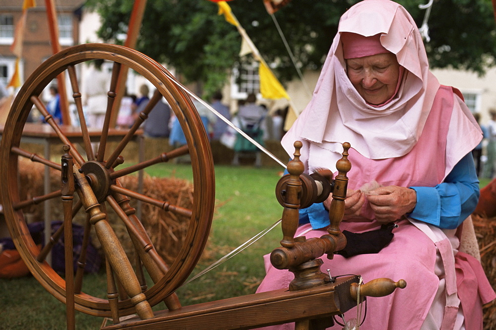 Woman in traditional costume demonstrating authentic spinning, Witham Medieval Fayre, Essex, England, United Kingdom, Europe
