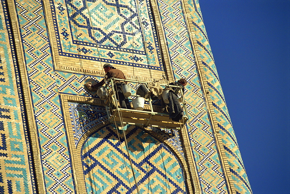 Workers in cradle refurbishing the 17th century Sher Dor Madressa, Registan Square, Samarkand, Uzbekistan, Central Asia, Asia