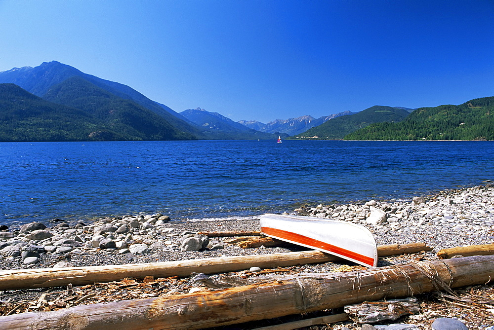 Upturned canoe on the rocky eastern shore of Slocan Lake, New Denver, British Columbia (B.C.), Canada, North America