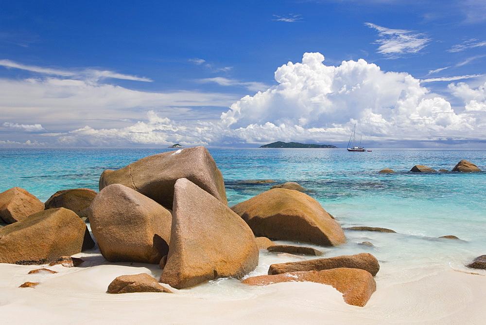 Granite boulders on the shore at Anse Lazio, island of Aride visible on horizon, Baie Sainte Anne district, Island of Praslin, Seychelles, Indian Ocean, Africa