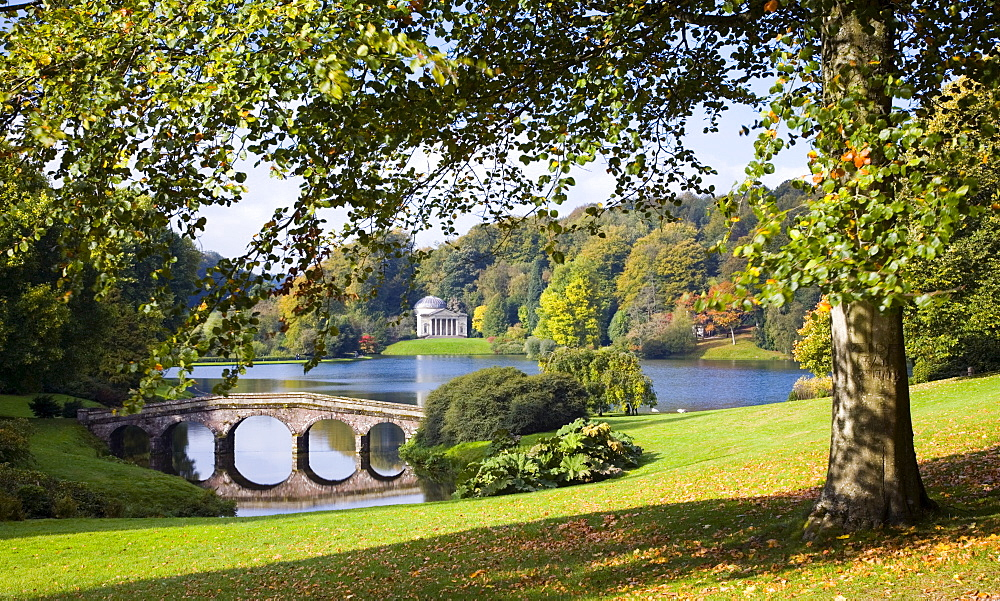 View across lake to the distant Pantheon in autumn, with Palladian bridge, Stourhead, near Mere, Wiltshire, England, United Kingdom, Europe