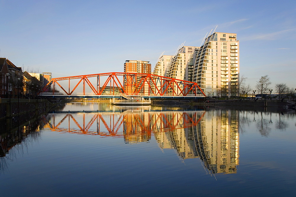 Residential tower blocks and colourful bridge reflected in water, Salford Quays, Salford, Greater Manchester, England, United Kingdom, Europe