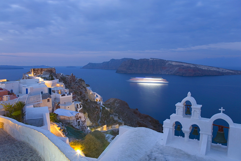 Illuminated cruise ship entering the caldera at dawn, Oia (Ia), Santorini (Thira) (Thera), Cyclades Islands, South Aegean, Greek Islands, Greece, Europe,