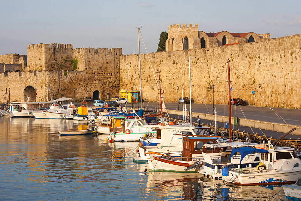View across tranquil Kolona Harbour to the city walls, sunrise, Rhodes Town, Rhodes, Dodecanese Islands, South Aegean, Greece, Europe - 390-2931