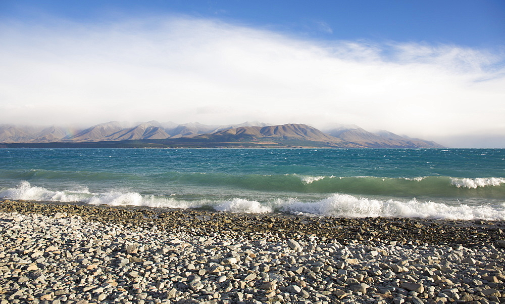 View from rocky shoreline across the stormy waters of Lake Pukaki, near Twizel, Mackenzie district, Canterbury, South Island, New Zealand, Pacific