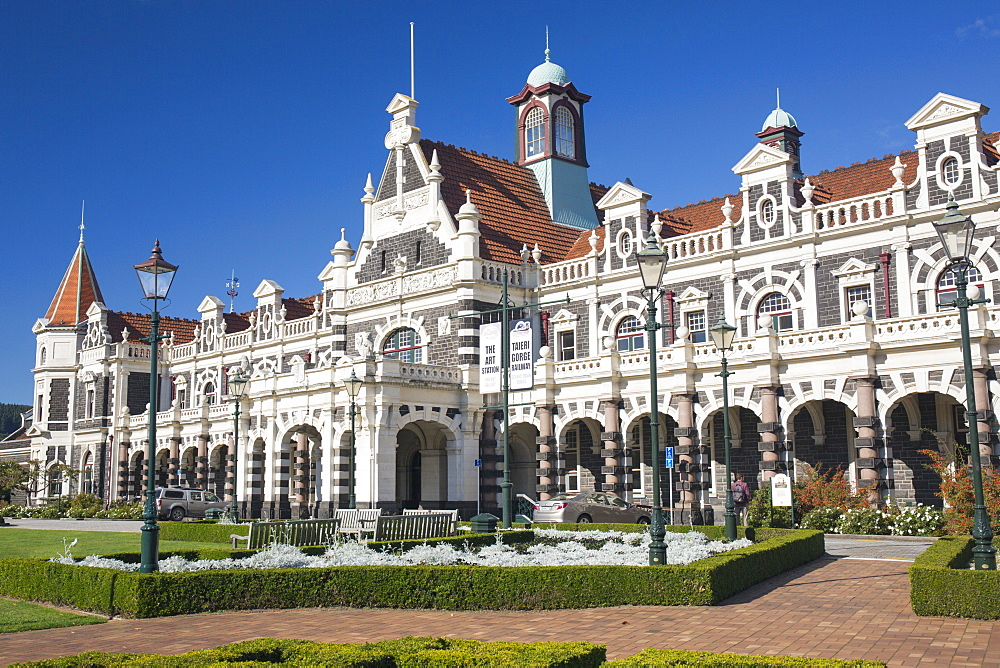 View from gardens to the imposing facade of Dunedin Railway Station, Anzac Square, Dunedin, Otago, South Island, New Zealand, Pacific