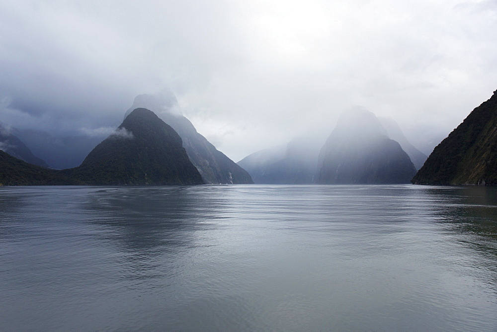 View down rainswept Milford Sound, mountains obscured by cloud, Milford Sound, Fiordland National Park, UNESCO World Heritage Site, Southland, South Island, New Zealand, Pacific