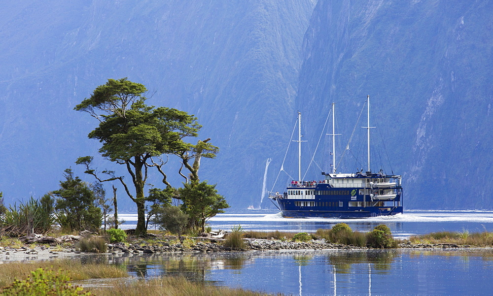 The Milford Mariner dwarfed by steep mountains, Milford Sound, Fiordland National Park, UNESCO World Heritage Site, Southland, South Island, New Zealand, Pacific